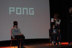 Moderator Samuel erklärt dem Publikum und den beiden Freiwilligen die Spielregeln